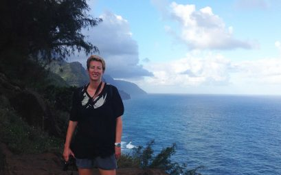 SueWhereWhyWhat standing on the cliffs over looking the sea on the Kalalau Trail in Hawaii with her camera. 10 Top Tips for Hiking as a Solo Female Traveller
