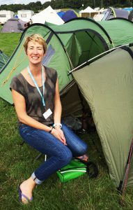 Oxfam volunteer weekend sitting smiling by a small green tent, backstage at Bestival Festival, Dorset England. How To Get A Free Ticket To A UK Music Festival and Help End World Poverty