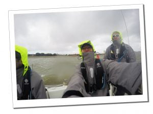 SueWhereWhyWhat, at the wheel, while taking her competent crew course sailing on The Solent off of the coast of the south of England in a grey wet weather jacket, UK