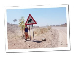 SueWhereWhyWhat with a sign for Elephants crossing on the road from Swakopmund to Sossusvlei, Namibia