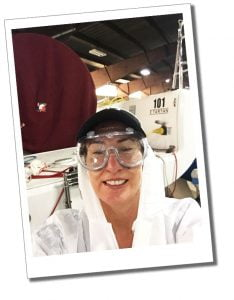 SueWhereWhyWhat in white protective clothing & goggles while sanding & maintaining, the yacht Red Hot in a shed