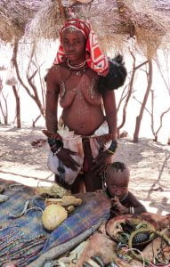 A Himba Tribeswoman and her child, selling necklaces and trinkets from a rug laid out in the shade, Namibia