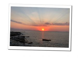 A beautiful orange sunset and rays across a darkening calm, blue grey sea, Naxos, Sunset, Greece