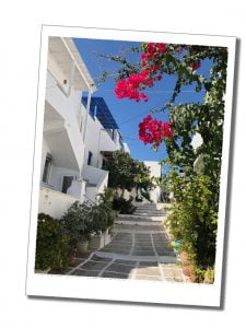 Shocking pink flowers light up a backstreet view in Paros, Greece