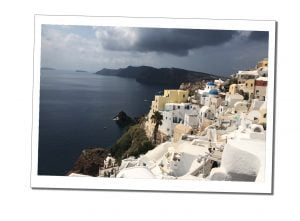 The white washed buildings of Oia, Santorini, clinging to the cliffs under a dark and brooding sky, Greek Islands