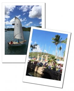 Nelsons Dockyard, Antigua as crowds enjoy the sunshine and a small sailing boat glides across the bay