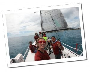SueWhereWhyWhat in red sunglasses smiling with the crew on a yacht during the St.Thomas' Regatta, USVI in the Caribbean