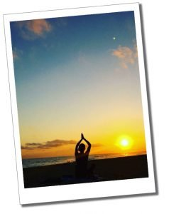 SueWhereWhyWhat sits striking a yoga pose at sunset on a Cuban beach