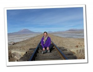 SueWhereWhyWhat in Purple top sitting in the middle of the deserted Train track to Chile in the Bolivian plains