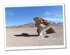 A Stone Tree (Arbol De Piedra) standing alone and throwing a large shadow in front of distant mountains, In The Bolivian Desert
