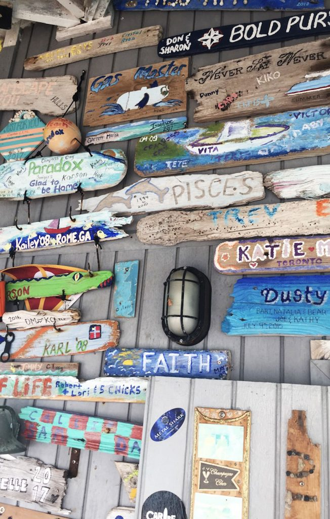 Painted wooden plaques at bar, Compass Cay, Bahamas