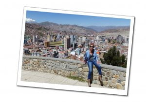 Suewherewhywhat sitting on a wall with a view of Mirador Killi, in La Paz, Bolivia
