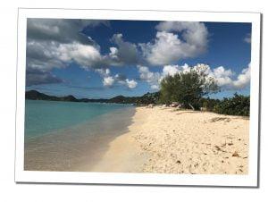 A sandy beach in a cloudy but sunny setting. Antigua