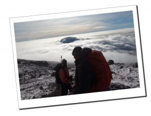 Guides above the clouds at the summit of Kilimanjaro, preparing for the decent
