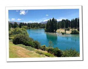 Calm azure waters viewed from the river bank at Queenstown, New Zealand