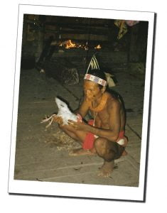 Villager holding a white chicken pre-sacrifice, Indonesia, Siberut - Crazy Travel Stories