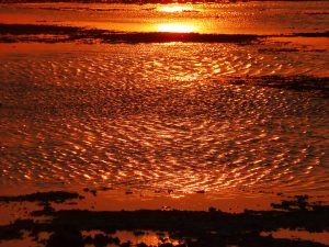 A stunning orange reflection turns the sea to flame at sunset, Bali