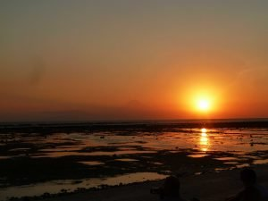 A stunning orange sky is punctuated by a fiery yellow sun at sunset over the now blackened beach, Bali