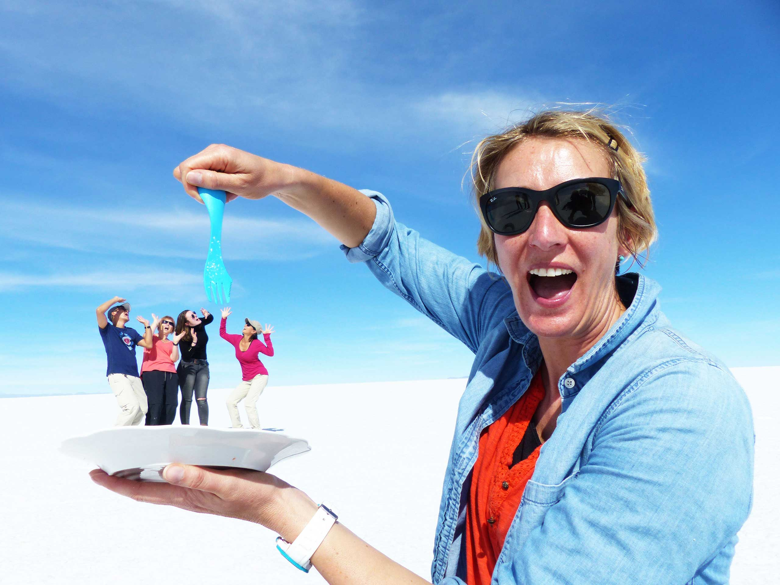 Suewherewhywhat is laughing as she pretends to eat 4 friends with a blue fork from a plate, using the flat perspective Salar de Uyuni (Salt Flats) & beyond
