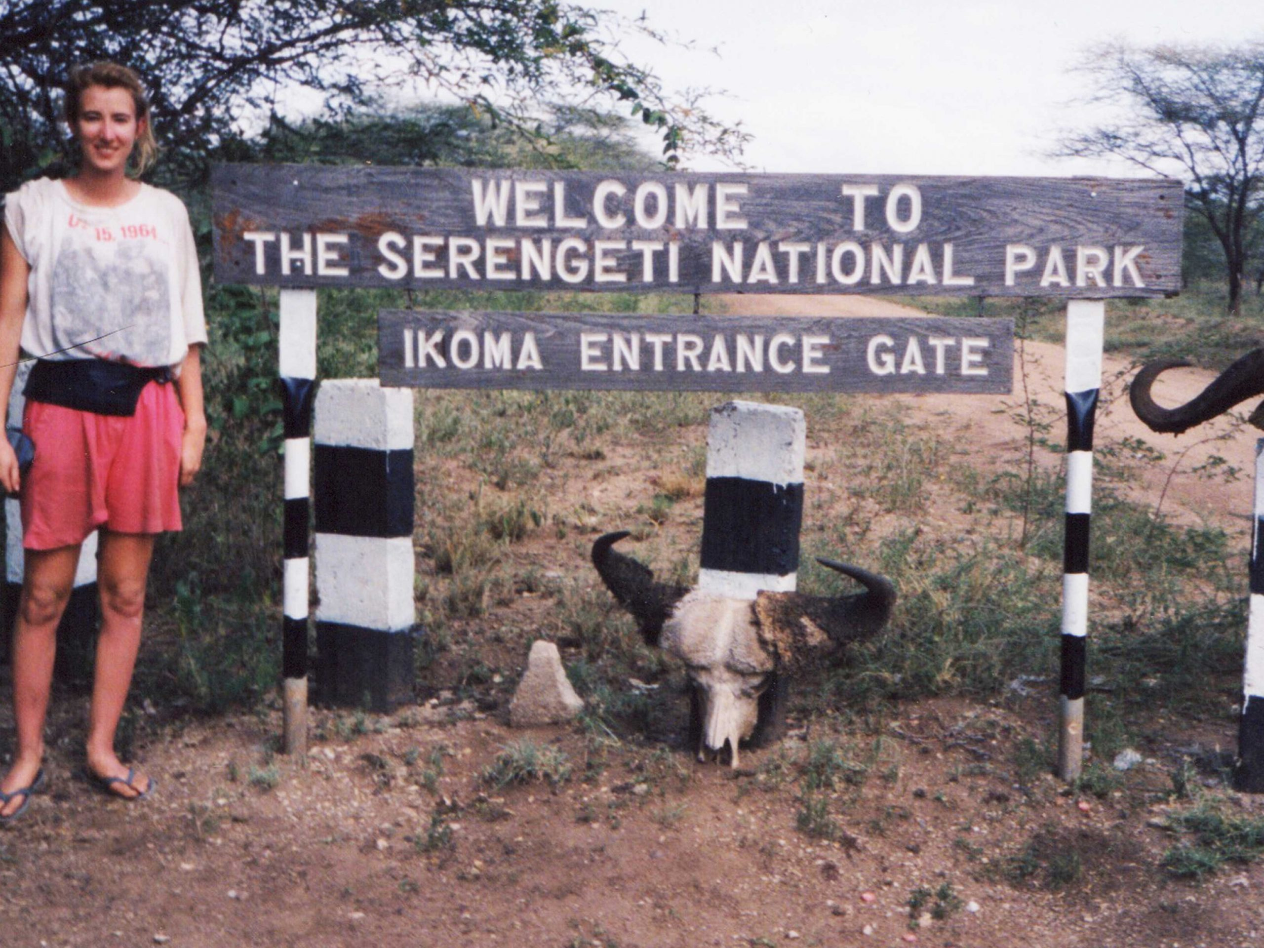 SueWhereWhyWhat standing by a wooden sign for the Serengeti National Park, Ikoma entrance, Africa 1992. 5 Ways to avoid being attacked by Lions!
