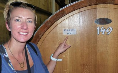 SueWhereWhyWhat, Standing in front of a large wooden vat of Wine, pointing to a sticker dated 3.9.15, vineyards, Australia.