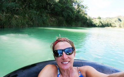 SueWhereWhyWhat in Sunglasses and bandana on the river float on big tyres. Dominican Republic.