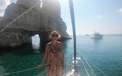 Suewherewhywhat standing in the sun at the front of the boat on Milos Boat tour at Kleftiko rocks