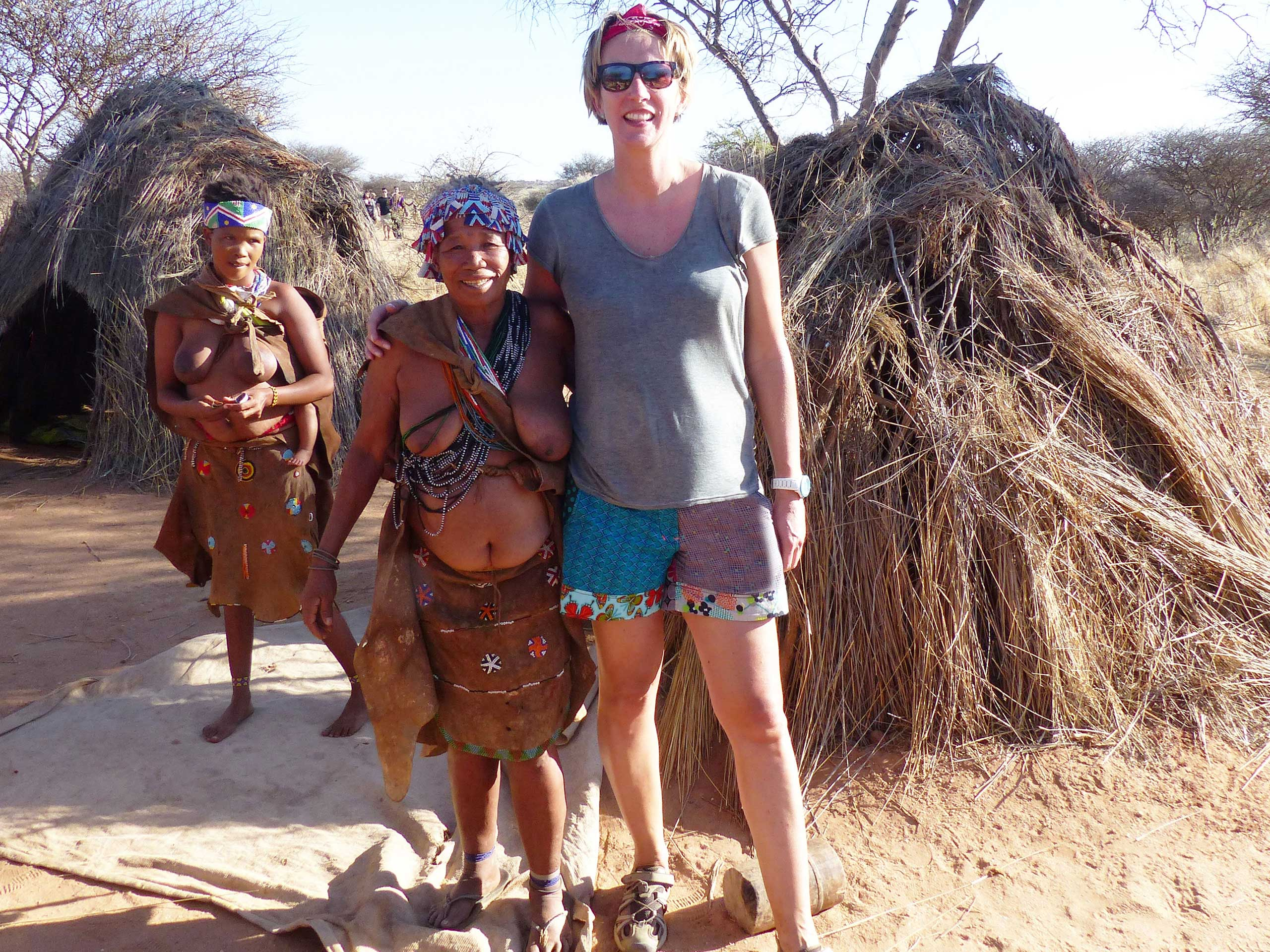 SueWhereWhyWhat towers of a woman from the San tribe outside her grass hut as a fellow tribeswoman looks on, Namibia. Volunteering in a Wildlife Sanctuary in Namibia - Week One
